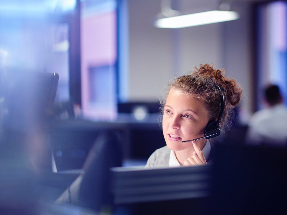 Woman working in an office using a headset
